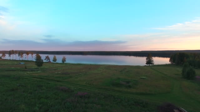 Flying out over lake at sunset in Northern Sweden. Aerial shot over summer landscape video