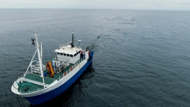 flying over a commercial fishing ship that pulls trawl net - fishing video stock e b–roll