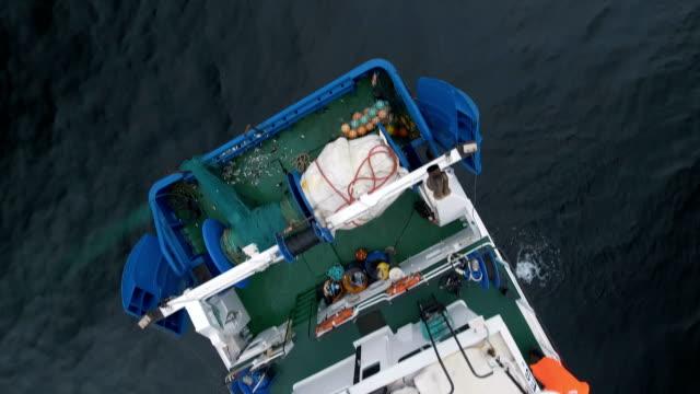 vídeos de stock, filmes e b-roll de voando sobre uma nave comercial de pesca com rede de arrasto no mar. - países bálticos