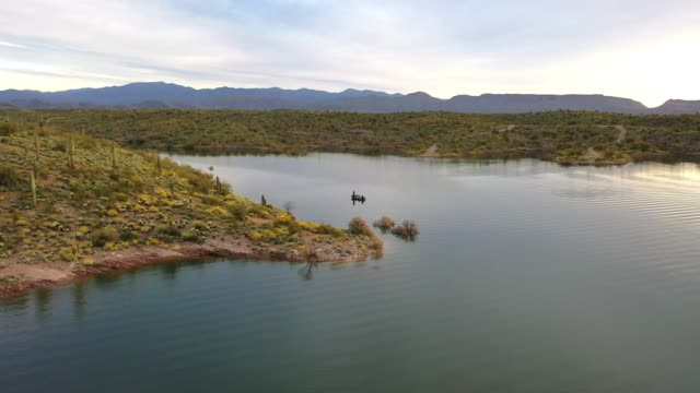 Flying over a lake with a man in his fishing boat enjoying the morning light