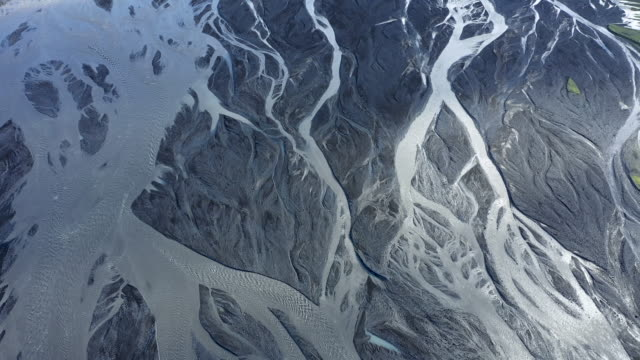 flying over a large icelandic glacial river system, delta in vatnajokull national park, iceland, showing unique natural geological patterns - ghiaccio galleggiante video stock e b–roll