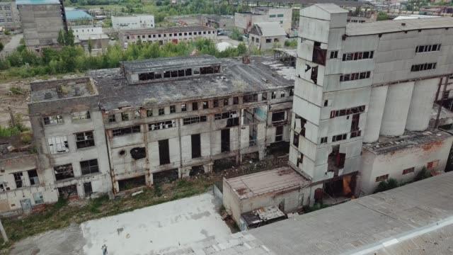 Flying over abandoned industrial factory buildings in very dilapidated condition.