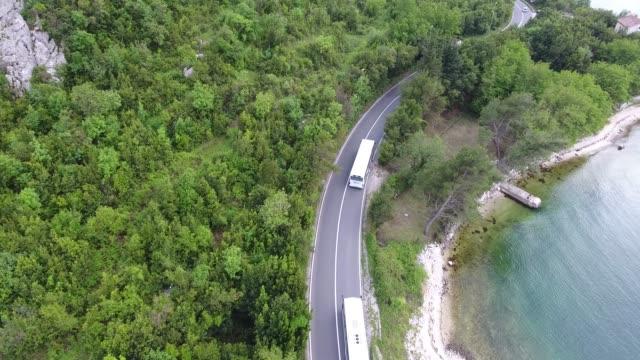 sorvolando una strada asfaltata che corre lungo la costa del mare. i veicoli stanno guidando lungo la strada - costa caratteristica costiera video stock e b–roll