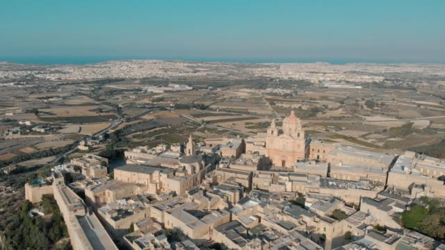 flying over ancient town with saint paul cathedral dome in mdina old town with old buildings, top view - insygnia filmów i materiałów b-roll