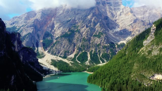 Flying over beautiful blue lake, forest and mountains in Switzerland. Landscape in aerial view with a drone 4K