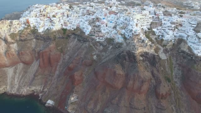 flying over beuatiful & famous oia on santorini island in greece during sunrise - fire filmów i materiałów b-roll