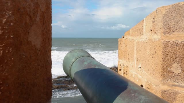 POV flying over cannon in old fortress to a view of the Atlantic ocean