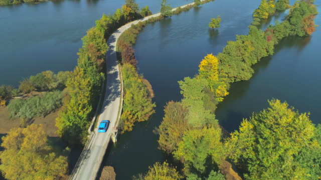 AERIAL: Flying over car driving down meandering road in submerged countryside. video