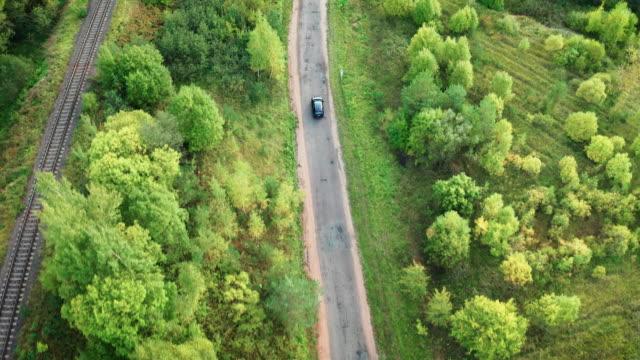 vídeos de stock, filmes e b-roll de sobrevoando carro dirigindo em estrada entre floresta verde, viajando por conceito de carro - veículo terrestre