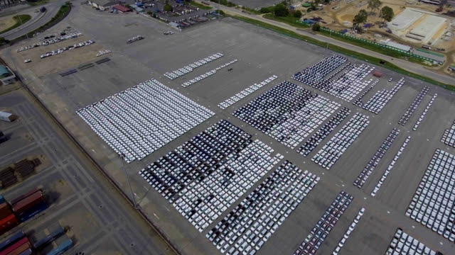 Flying over Car import parking lot, car line up, containers, ship, industrial port video
