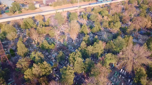 flying over cemetery. some graves are well-kept, while others are old, abandoned