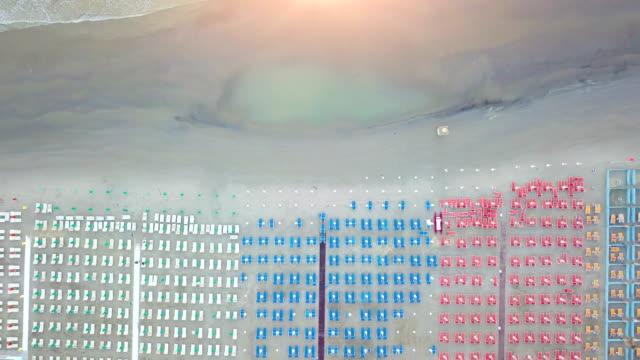 flug über geschlossene sonnenschirme und liegestühle an riviera der romagna bei sonnenaufgang - sonnenschirm stock-videos und b-roll-filmmaterial