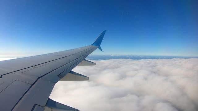 sorvolando le nuvole tra il cielo blu sull'aereo. vista del passeggero dal finestrino dell'aeromobile - aeroplano video stock e b–roll