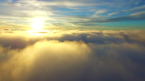 Flying over clouds Incredible aerial footage of a drone flying through the tops of the clouds and flying towards the sun. high up stock videos & royalty-free footage