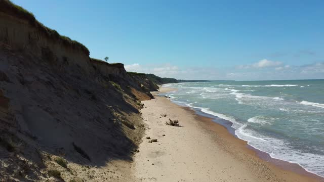 vídeos de stock e filmes b-roll de flying over coastline baltic sea ulmale seashore bluffs near pavilosta, latvia and landslides with an overgrown, rippling cave dotted cliff and pebbles. - letónia
