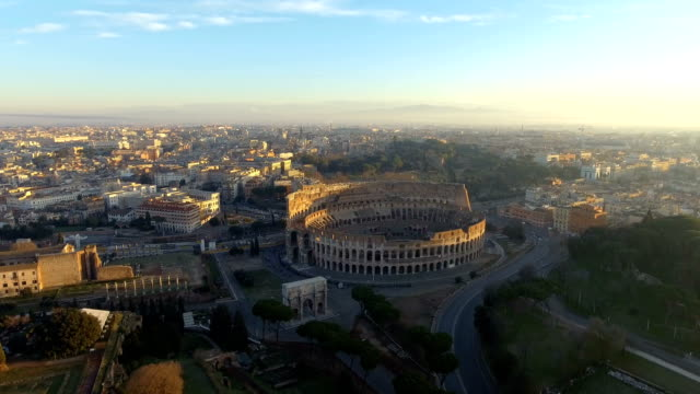 Flying over Colosseum, Rome, Italy. Aerial view of the Roman Coliseum on sunrise