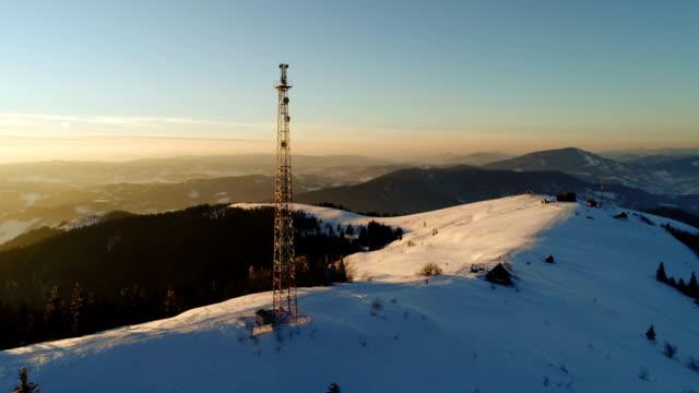 vídeos de stock, filmes e b-roll de sobrevoando a torre de comunicações, cobertas de neve de montanha, paisagem de inverno - meteorologia