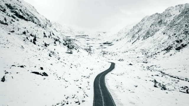 Flying over empty hairpin curve between snowy mountains Flying over empty hairpin curve between snowy mountains snowcapped mountain stock videos & royalty-free footage