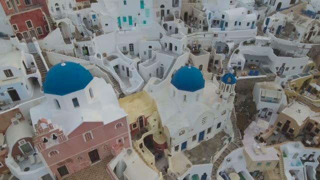 flying over famous 3 blue domes in oia on santorini island in greece - church architecture stock videos & royalty-free footage