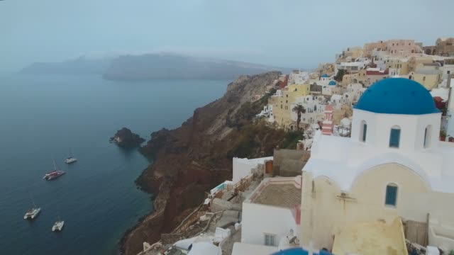 flying over famous 3 blue domes in oia on santorini island in greece - fire filmów i materiałów b-roll