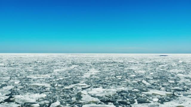 vídeos de stock, filmes e b-roll de voando sobre o mar de gelo a flutuar em dia ensolarado - países bálticos