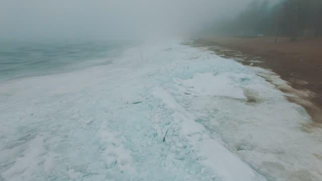 霧の寒い冬の日には凍った海の海岸線上空を飛行 ビデオ