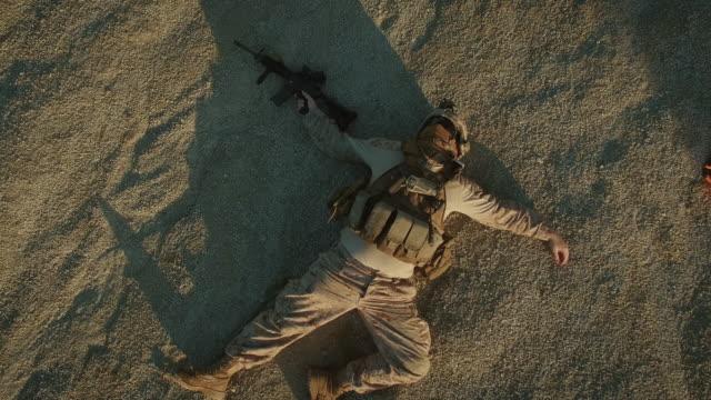 sorvolando il gruppo di soldati morti nell'area deserta. zoom indietro. - morto video stock e b–roll