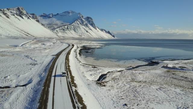 vídeos y material grabado en eventos de stock de volando sobre la carretera helada con paisaje de montaña nevado en invierno de la costa este de islandia - helado condición