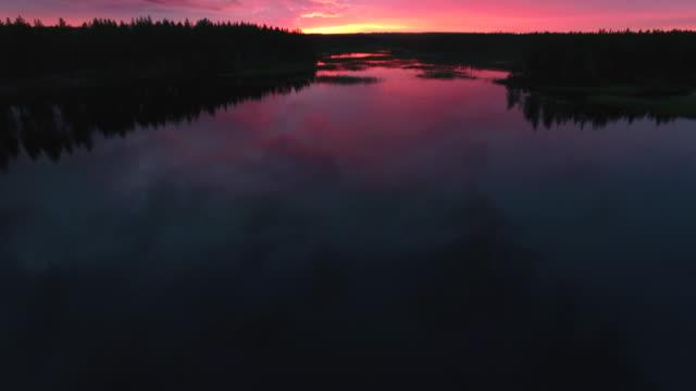 flygande över sjön vid solnedgången. antenn skott av sjön och vacker himmel i skymningen - pine forest sweden bildbanksvideor och videomaterial från bakom kulisserna
