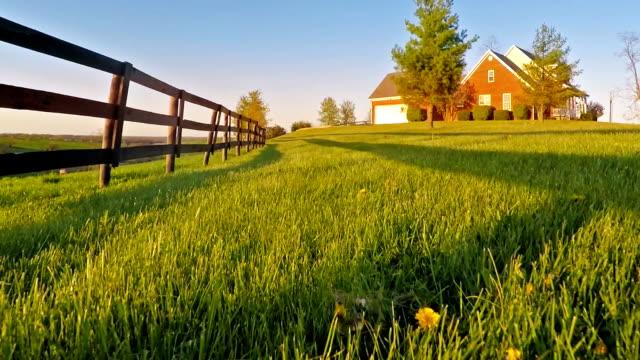 stockvideo's en b-roll-footage met flying over lawn - fence