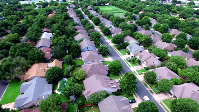 aerial: flying over local austin texas housing complex with natural trees and texas hill country feel backing up - proprietario d'immobili video stock e b–roll