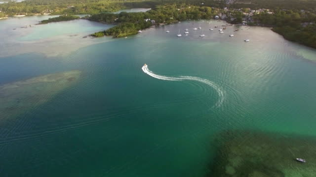 flying over motor boat sailing in bay, mauritius island - isole mauritius video stock e b–roll