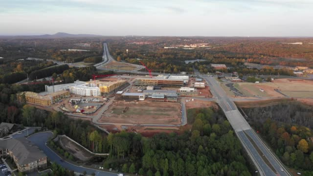 Flying over new mall construction next to condos and highway in Atlanta Suburbs
