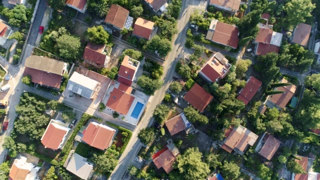 Flying over single family homes and villas that have swimming pools, surrounded by green flora. Aerial top down shot, UHD