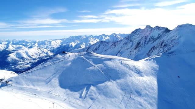 stockvideo's en b-roll-footage met vliegen over skiliften en ski-pistes. luchtfoto uitzicht over skiliften in besneeuwde berg. perfect weer voor skiën en snowboarden in de winter. - sneeuwkap
