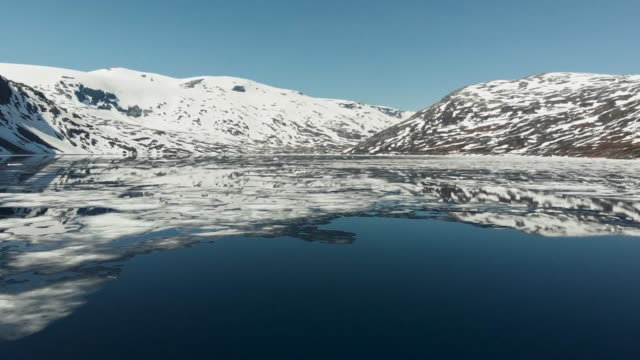 flying over spring lake with cracking ice floe. norway. uhd, 4k - ghiaccio galleggiante video stock e b–roll