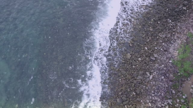 Flying over stones and pebbles in a beach shore bathed by sea waves