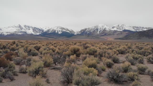 vidéos et rushes de aérien: en survolant le désert stérile sous la spectaculaire montagne enneigée - paysage extrême