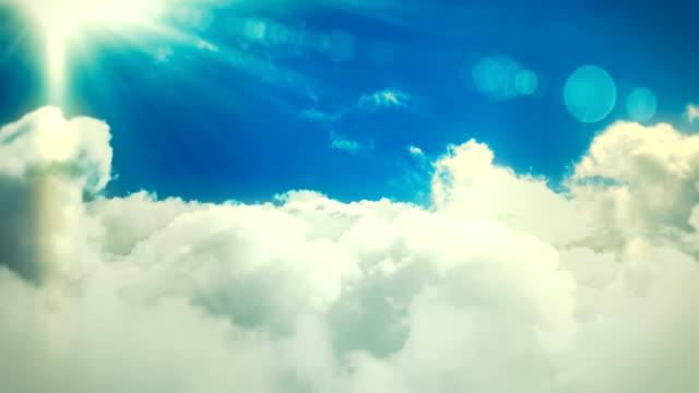 Flying over the clouds with sun and lensflares loopable cloudscape background animation