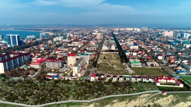 Flying over the coastal town in Russia, Anapa, at sunny day. Aerial view at city and sea bay.