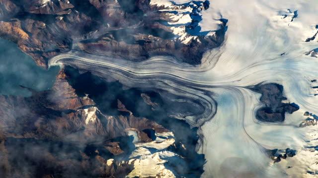 iss üzerinde uçan toprak üzerinde. uçan hava alanı görünümünden karla kaplı dağların üzerinden. - mountain top stok videoları ve detay görüntü çekimi