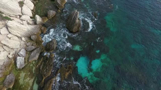 Flying over the edge of the sea. The scree of rocks from the shore of the island of Corsica