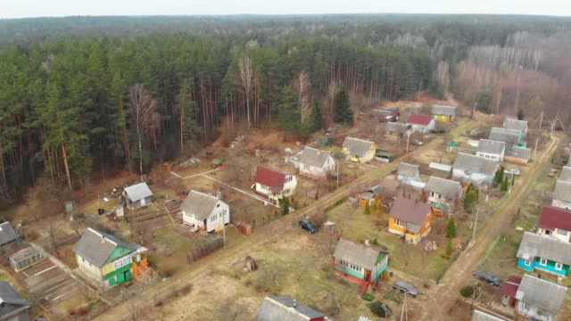 flying over the holiday village. early spring, dry grass - albero spoglio video stock e b–roll