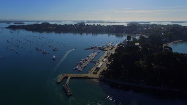 vidéos et rushes de volant au-dessus du petit port de le «île de moines», situé dans le fameux golfe du morbihan, morbihan, bretagne, france. cette baie est l'une des plus belles baies du monde. - bretagne