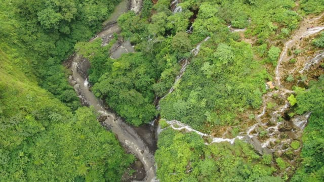 Flying over the mountain river in tropical forest