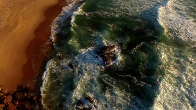 Flying over the ocean cliffs at sunset aerial Guincho Portugal video