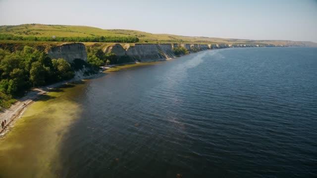 崖に沿って川の上を飛ぶ - マルチコプター点の映像素材/bロール