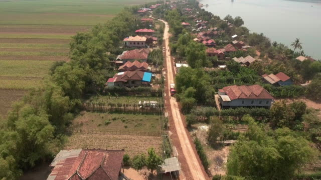 Flying over truck driving on a rural road through a village along the river video