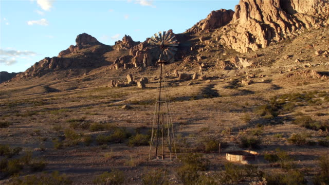 AERIAL: Flying over vintage windmill in sunny rocky mountain desert video