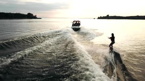 vidéos et rushes de survoler le wakeboarder surf derrière le bateau. vue aérienne du wakeboard sur la rivière au coucher du soleil. - transport nautique